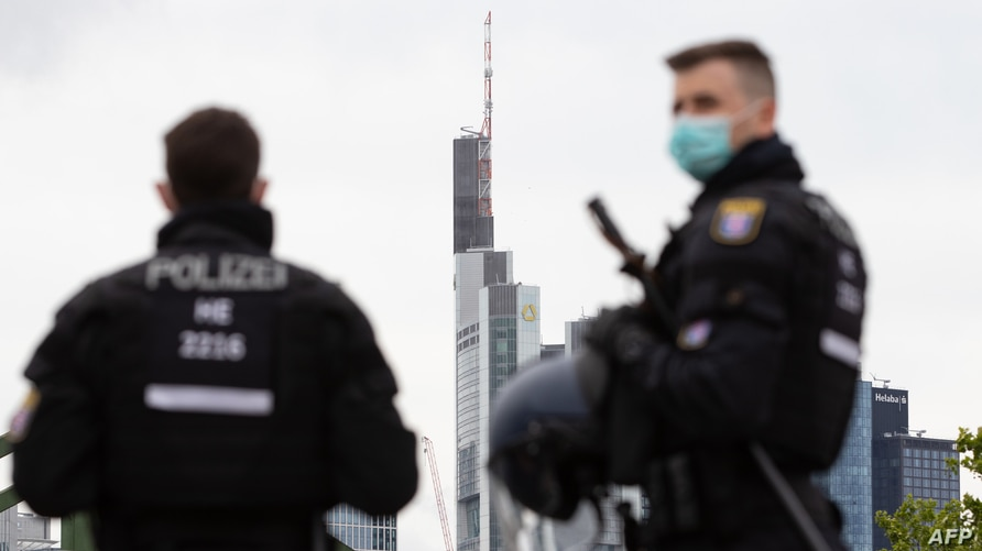 FILE - Police officers wearing face masks are pictured during a rally against restrictions in place to limit the spread of the coronavirus, in Frankfurt, Germany, May 23, 2020.
