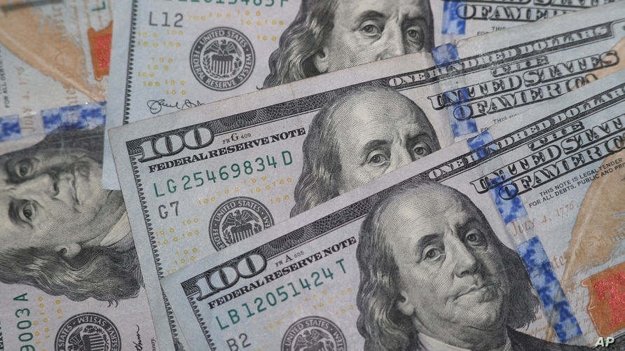 FILE - $100 bills with the likeness of Benjamin Franklin are photographed in Dallas, Texas, Jan. 22, 2020.