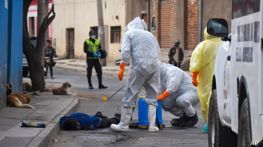 Health workers disinfect the body of a street vendor who was found dead by his neighbors in the Cerro San Miguel neighborhood of Cochabamba, Bolivia, July 25, 2020.