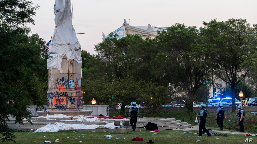 Police walk around at the site of the covered Christopher Columbus statue after protesters attempted to topple the statue located in Roosevelt and Columbus Dr. in Chicago, July 17, 2020. (Credit: Tyler LaRiviere/Chicago Sun-Times)