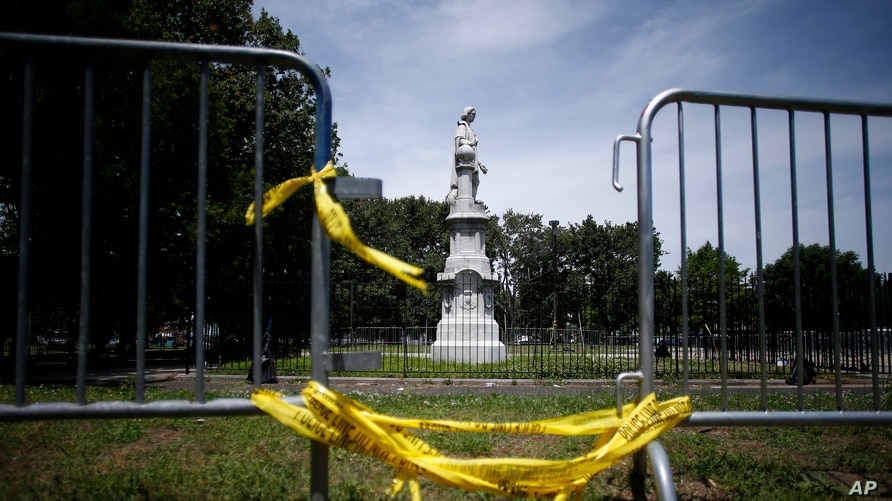 FILE - A statue of Christopher Columbus is seen behind barricades at Marconi Plaza, in Phalidelphia, Pennsylvania, June 15, 2020. A similar statue of Columbus was toppled by protesters in Baltimore, Maryland, July 4, 2020.