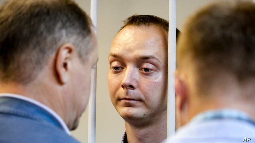 FILE - Ivan Safronov, an adviser to the director of Russia's state space corporation, stands behind bars in a courtroom in Moscow, Russia, July 7, 2020.