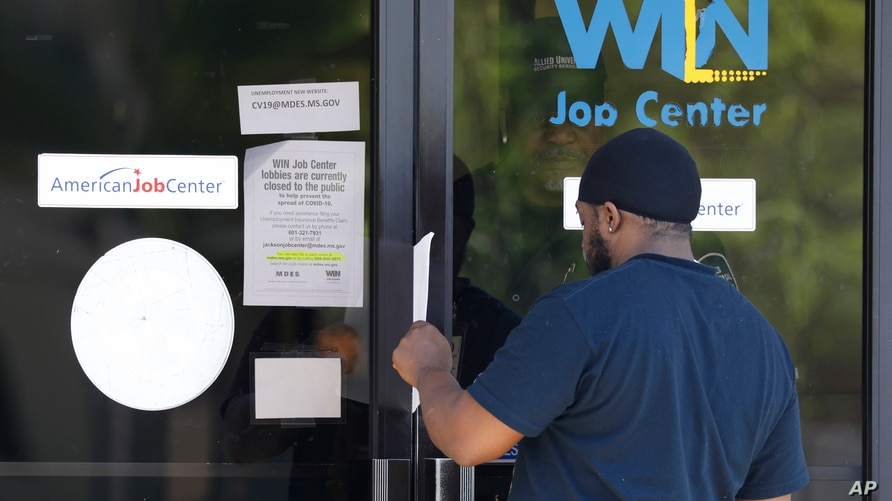 FILE - A man is handed an unemployment benefit application form by a security guard from behind glass doors of a state WIN Job Center in north Jackson, Mississippi, April 2, 2020.