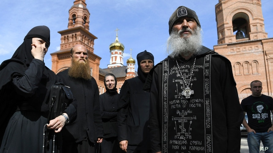 Father Sergiy, a Russian monk who has defied the Russian Orthodox Church's leadership, right, speaks with journalists in Sredneuralsk, Russia, June 17, 2020.