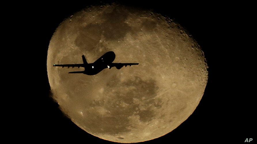 FILE - A passenger jet passes in front of a waning moon after taking off from Phoenix Sky Harbor International Airport, in Phoenix, Arizona, Feb. 11, 2020.