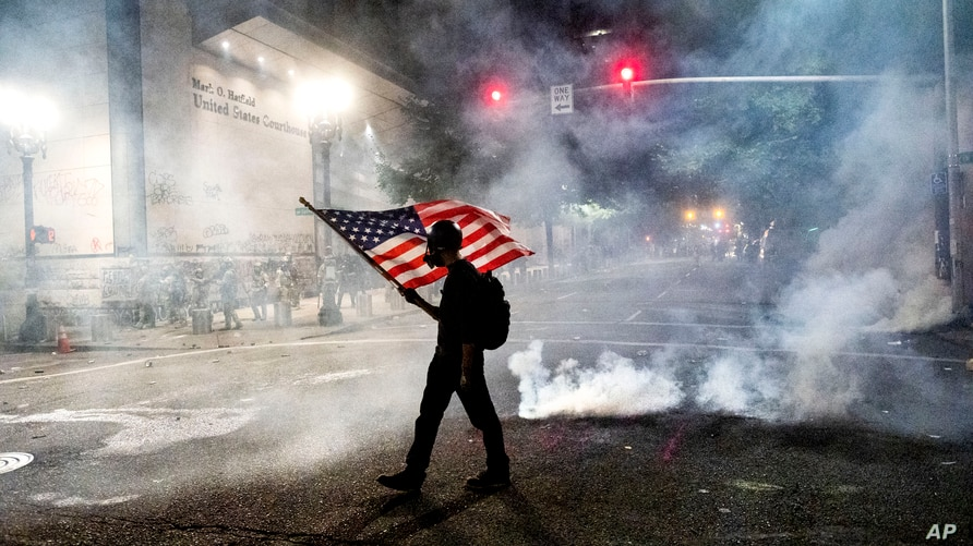 A Black Lives Matter protester carries an American flag as teargas fills the air outside the Mark O. Hatfield United States Courthouse in Portland, Oregon, July 21, 2020.