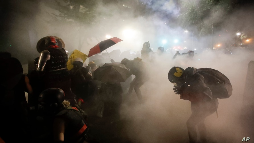 Federal officers launch tear gas at a group of demonstrators during a Black Lives Matter protest at the Mark O. Hatfield United States Courthouse in Portland, Oregon, July 26, 2020.