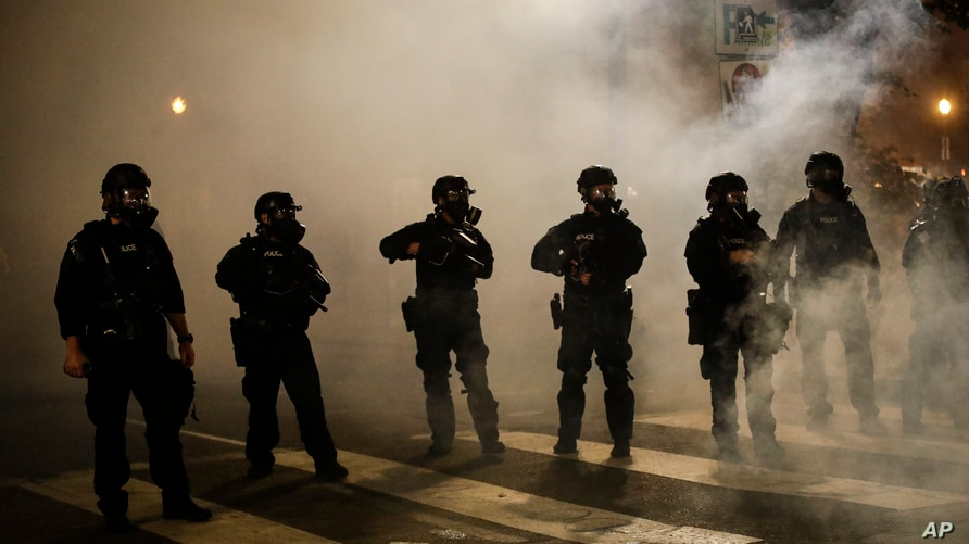 Federal officers are surrounded by smoke as they push back demonstrators during a Black Lives Matter protest at the Mark O. Hatfield United States Courthouse in Portland, Oregon, July 29, 2020.
