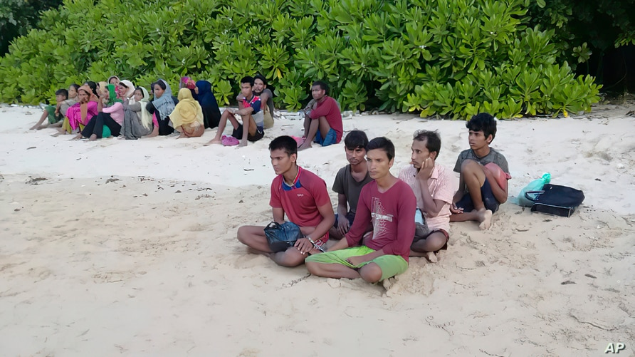 A photo taken July 26, 2020, by the Malaysian Maritime Enforcement Agency, shows Rohingya refugees, who were thought to have drowned, sitting on a beach on Rebak Island, off the resort island of Langkawi, Malaysia.