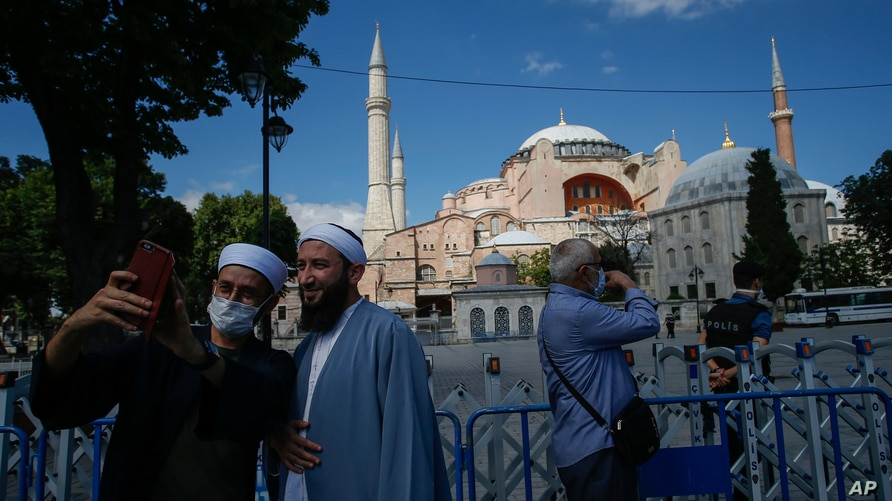 FILE - People use their mobile phone to take a selfie outside the Byzantine-era Hagia Sophia, one of Istanbul's main tourist attractions in the historic Sultanahmet district of Istanbul, Turkey, July 11, 2020.