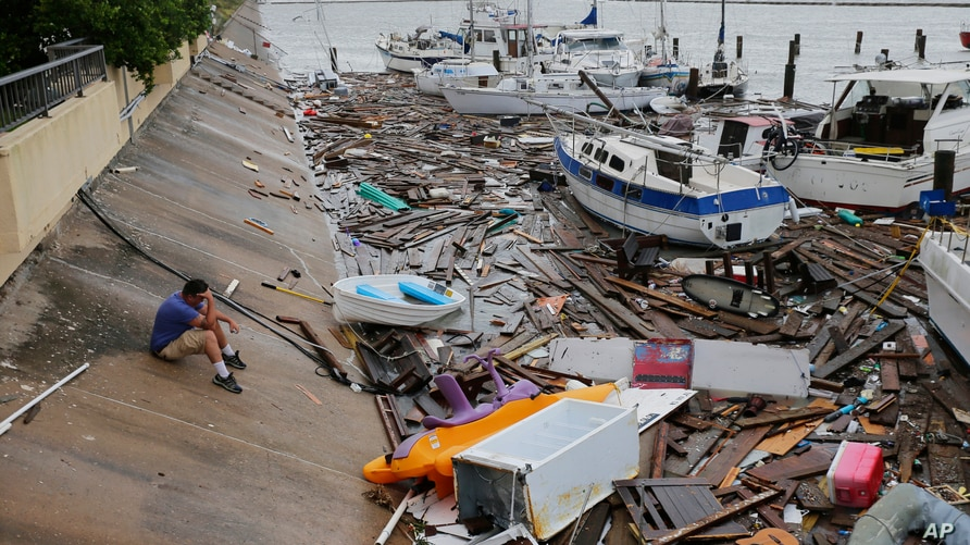 Allen Heath surveys the damage to a private marina after it was hit by Hurricane Hanna in Corpus Christi, Texas.