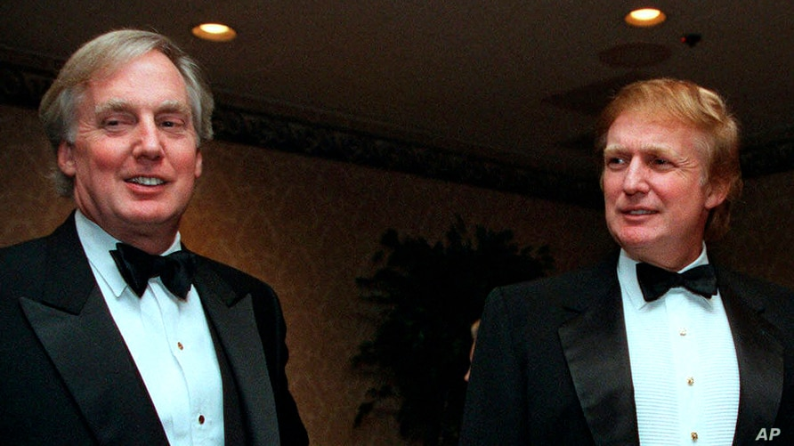 FILE - Robert Trump (L) joins his brother, then real estate developer Donald Trump, at an event in New York, Nov. 3, 1999. A court has ruled that a tell-all book by President Donald Trump's niece now can be distributed despite Robert Trump's objections.