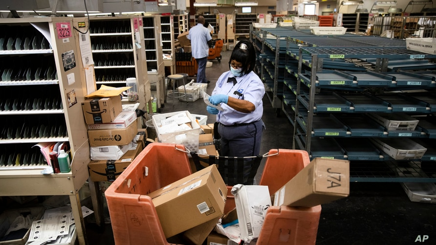 FILE - A United States Postal Service carrier sorts mail to be delivered before she sets out on her route in Philadelphia, Pennsylvania, May 6, 2020.