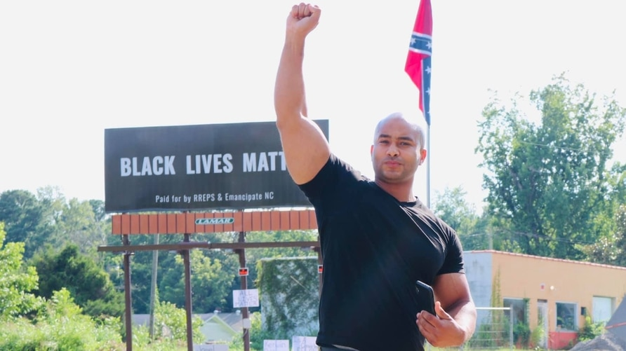 Kerwin Pittman, founder of Recidivism Reduction Educational Program Services, poses in front of the Black Lives Matter billboard set next to a Conferedate flag in a photo from his Facebook page. (Photo by Bee Ess)