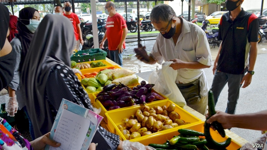 A man selects fresh produce at a mobile food bank run by Kechara in Kuala Lumpur. (Zsombor Peter/VOA)