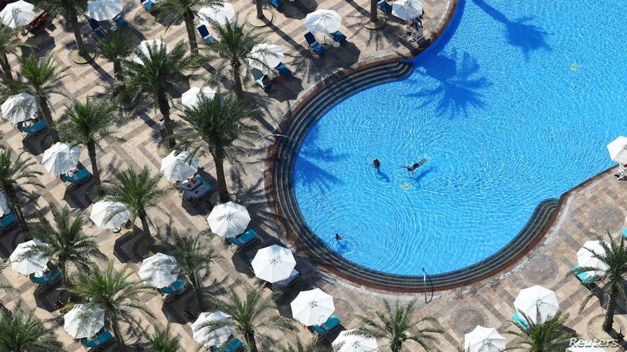 People are seen in a swimming pool at the Atlantis, The Palm Hotel, as the Emirates reopen to tourism amid the coronavirus pandemic, in Dubai, United Arab Emirates, July 7, 2020.