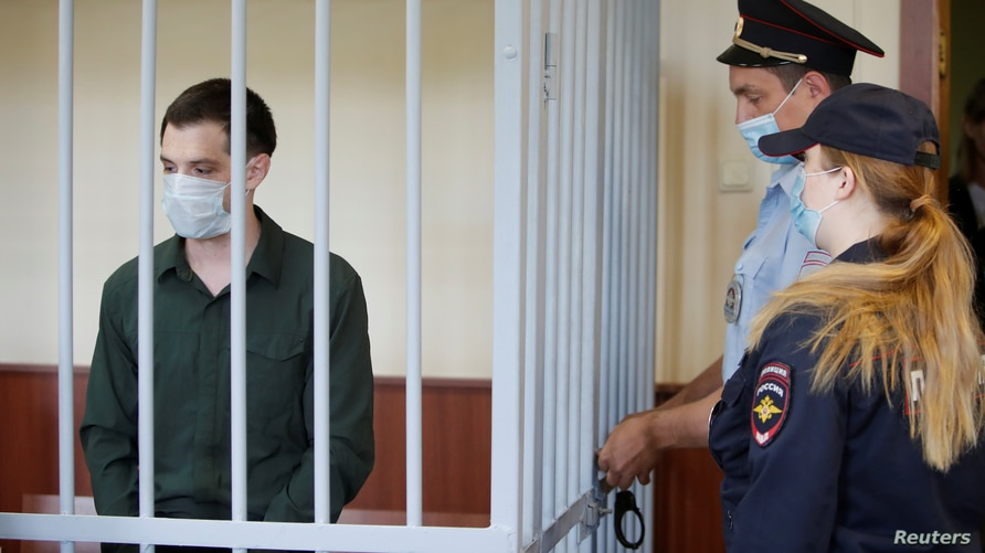 Former U.S. Marine Trevor Reed, who was detained in 2019 and accused of assaulting two police officers, stands inside a defendant's cage during a court hearing in Moscow, Russia, July 30, 2020.