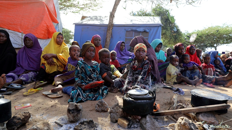 FILE - Somali families, displaced after fleeing the Lower Shabelle region amid an uptick in U.S. airstrikes, sit under a tree at an IDP camp near Mogadishu, Somalia, March 12, 2020.