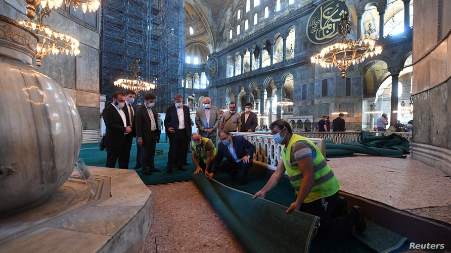 The head of Turkey's Religious Affairs Directorate, Ali Erbas, visits Hagia Sophia as workers lay carpets in its interior, in Istanbul, Turkey, July 22, 2020.