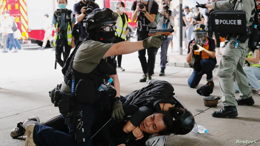 A police officer raises his pepper spray handgun as he detains a man during a march against the national security law at the anniversary of Hong Kong's handover to China from Britain in Hong Kong, July 1, 2020.