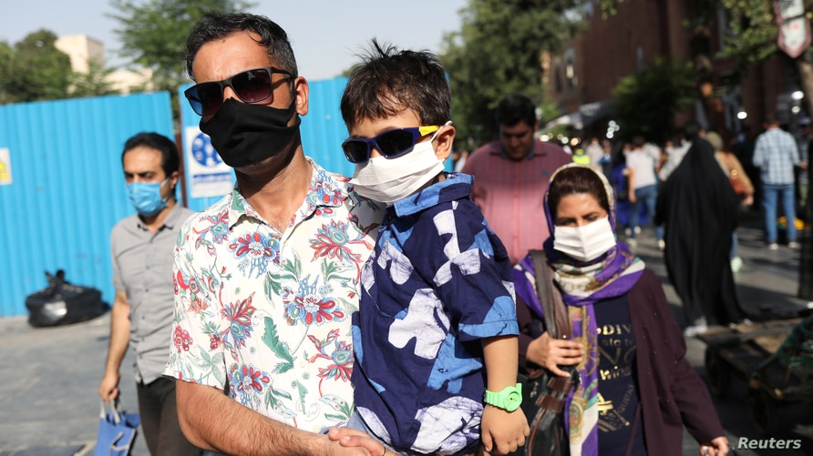 People wearing protective face masks walk in a street, following the outbreak of the coronavirus disease (COVID-19), in Tehran, Iran, June 28, 2020.