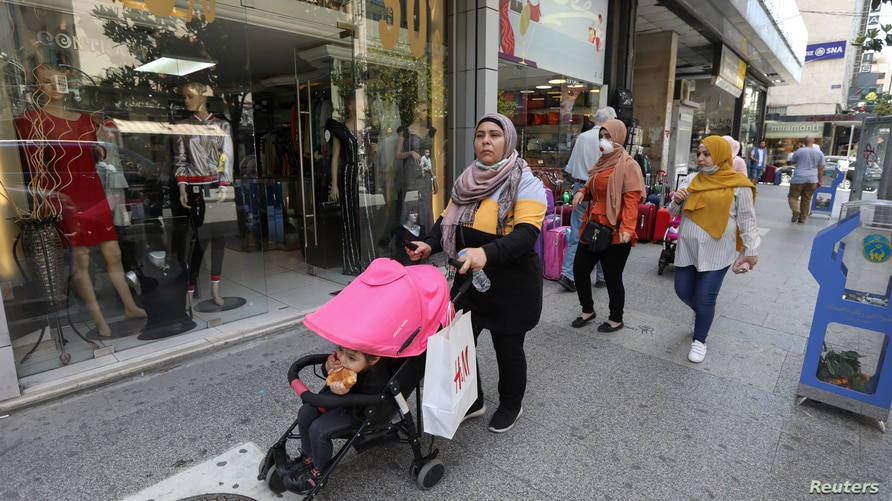 Women walk past open shops, as Lebanon is gradually reopening its economy following a four-day shutdown imposed to curb the spread of coronavirus disease (COVID-19) in Hamra street in Beirut, May 18, 2020.