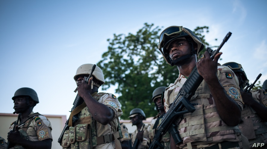 Soldiers conduct the daily flag-lowering ceremony at the Force Multinationale Mixte (FMM) base in Mora, in Cameroon's Far North…