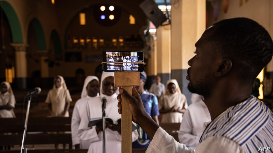 A man uses a phone to broadcast the traditional Easter Sunday mass live on social media at the Cathedral of the Immaculate Conception in Ouagadougou, on April 12, 2020. Collective prayers and gatherings have been suspended in Burkina Faso as a precautionary measure against the spread of the COVID-19 coronavirus.