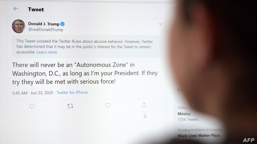 This illustration photo shows a woman in Los Angeles looking at the official Twitter account of US President Donald Trump on…
