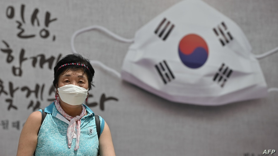 A woman walks in front of a banner showing a face mask displayed on the wall of the city hall in Seoul on August 20, 2020. …
