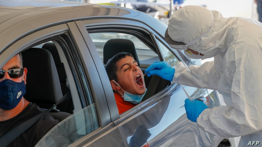 A paramedic with Israel's Magen David Adom (Red Shield of David) national emergency medical service, performs a swab test at a…