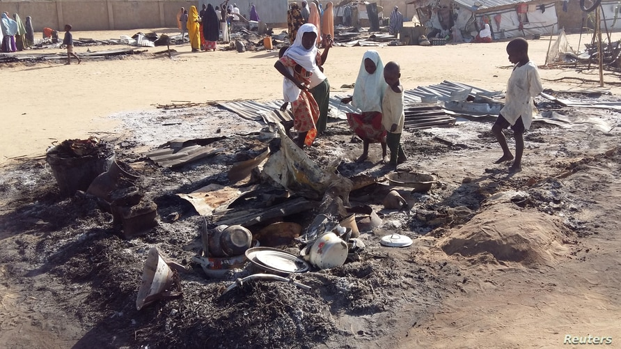People stand amid the damage at a camp for displaced people after an attack by suspected members of the Islamist Boko Haram…
