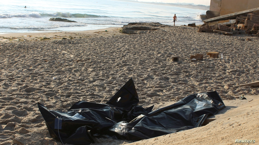 Bags containing the bodies of migrants who died after their wooden boat capsized off the coast of Komas, are seen in the town…