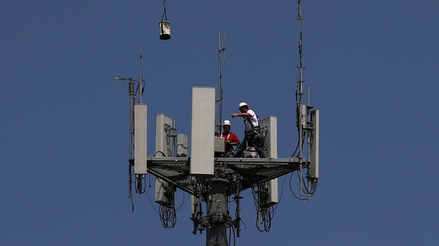 Workers install 5G telecommunications equipment on a T-Mobile US Inc tower in Seabrook, Texas, U.S. May 6, 2020. REUTERS/Adrees…