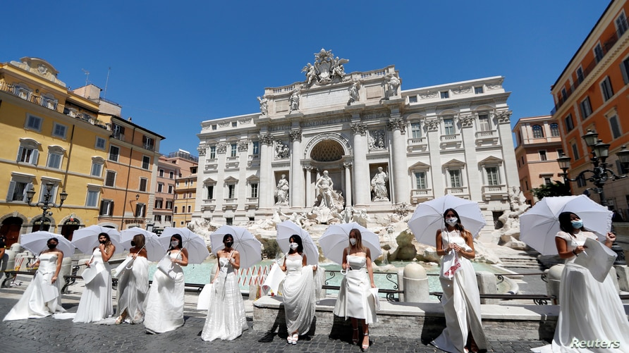Brides wearing wedding dresses hold a flash mob near Trevi fountain to protest against the postponement of their weddings due…