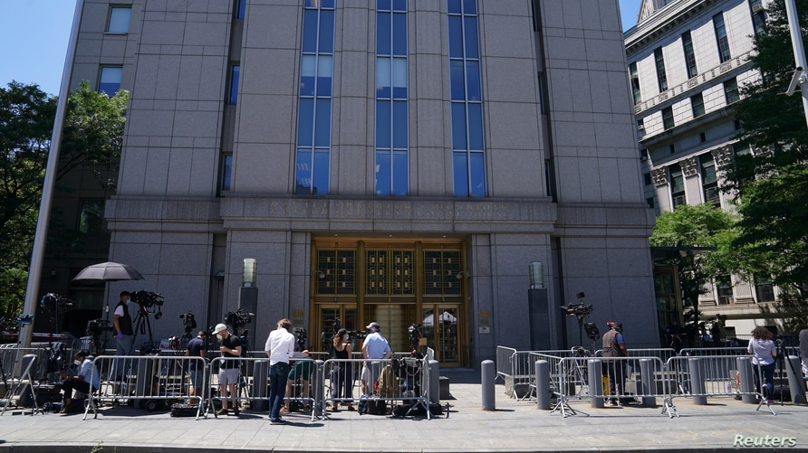 Media wait outside federal court for a bail hearing in the Ghislaine Maxwell case in the Manhattan borough of New York City,…