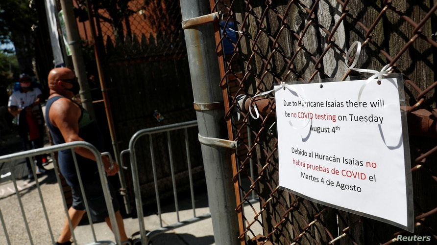 A sign informing that Tuesday testing will be canceled due to Hurricane Isaias is seen outside a community testing center for…