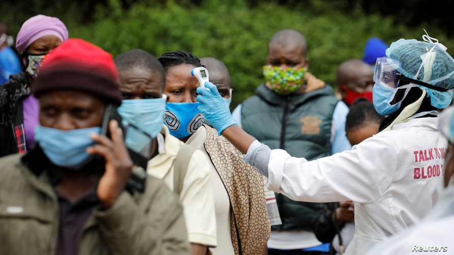 FILE PHOTO: A health worker takes the temperature of a person standing in line for mass testing in an effort to stop the spread…