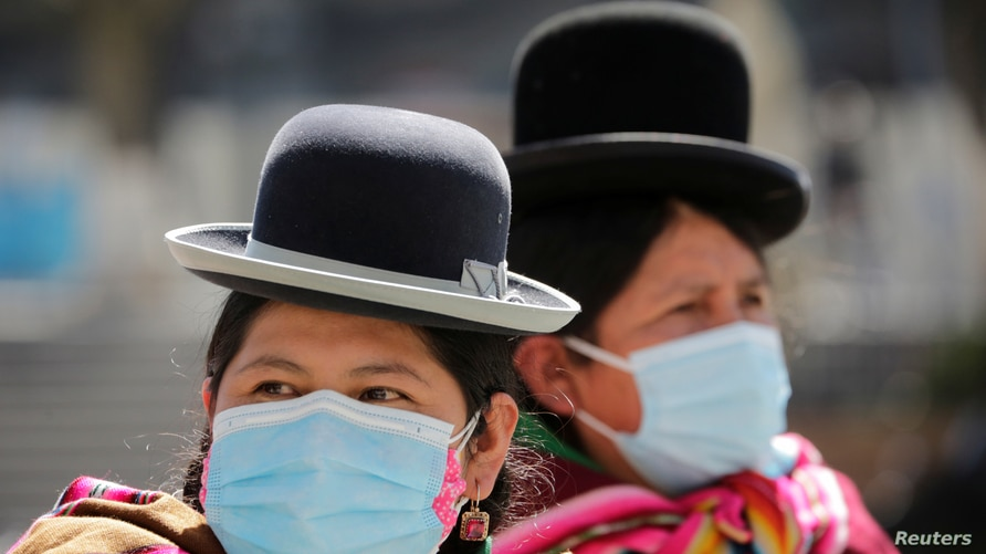 Aymara indigenous women wearing protective masks are seen at the Plaza Murillo during a celebration marking the 195th…