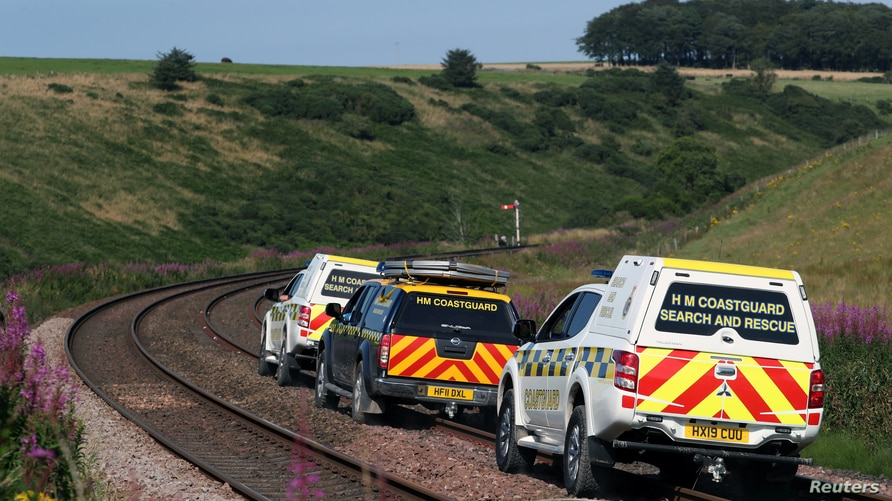 Emergency service vehicles ride along the tracks near the scene of a derailed passenger train, near Carmont, Stonehaven,…