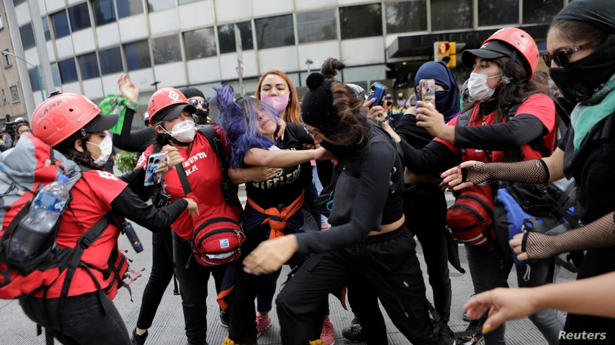 Members of NGO Independent Space Marabunta try to stop a fight among protesters