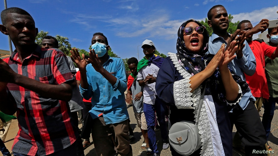 Sudanese protesters march in a demonstration to mark the anniversary of a transitional power-sharing deal with demands for…