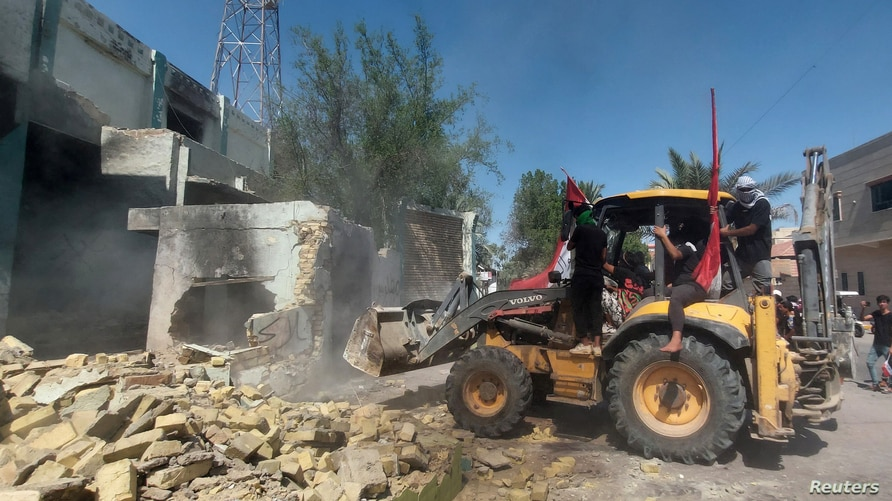 Protesters use a bulldozer to demolish offices of Shi'ite parties during ongoing anti-government protests in Nasiriya, Iraq…