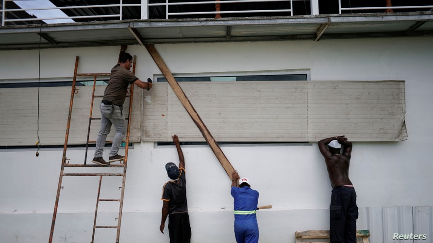 Workers protect the windows of a bar in anticipation of the Tropical Storm Laura arrival, in Havana, Cuba, August 24, 2020…