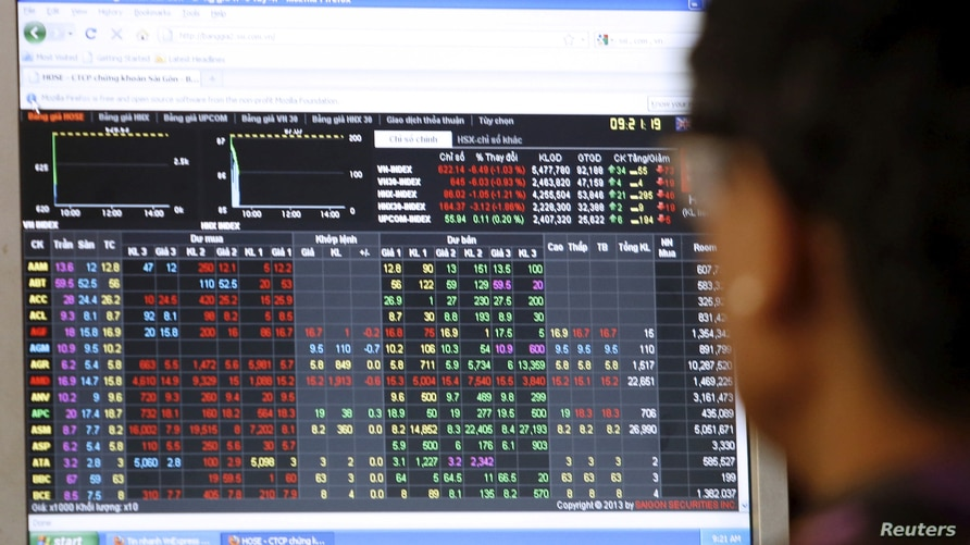 FILE PHOTO: FILE PHOTO: An investor looks at a stock market screen at a securities company in Hanoi, Vietnam. July 20, 2015…