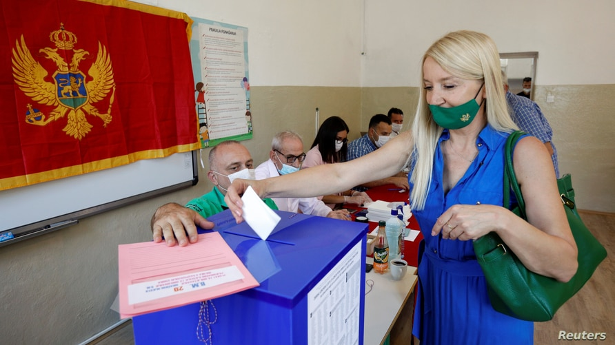 A woman wearing a face mask due to the ongoing coronavirus disease (COVID-19) outbreak casts her vote at a polling station…