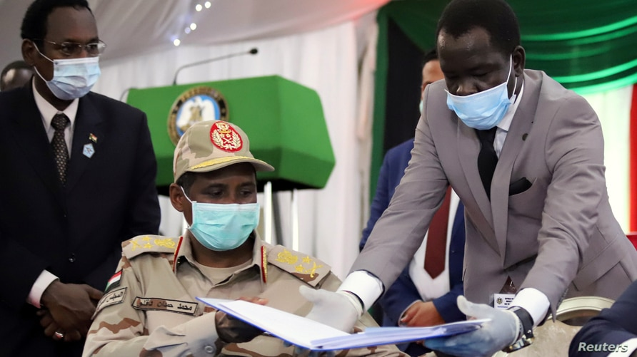 Lt. Gen. Mohamed Hamdan Dagalo, deputy head of the military council, reveives a peace agreement to sign between Sudan's power-sharing government and five key rebel groups, Juba, South Sudan, Aug, 31, 2020.