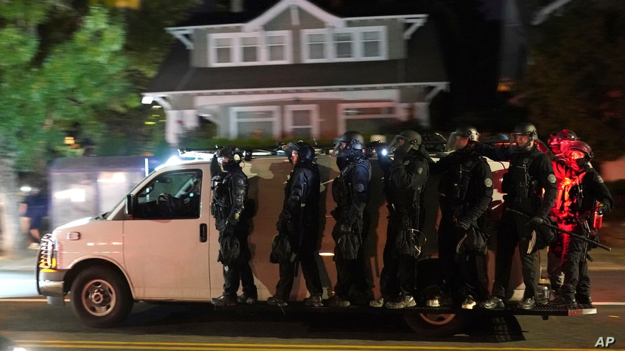 Portland police search for protesters in the Laurelhurst neighborhood after dispersing a crowd of about 200 people from in front of the Multnomah County Sheriff's Office in Portland, Oregon, Aug. 8, 2020.