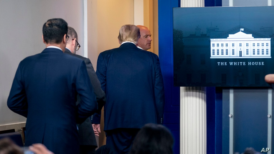 President Donald Trump is asked to leave the James Brady Press Briefing Room by a member of the U.S. Secret Service during a news conference at the White House, Aug. 10, 2020.