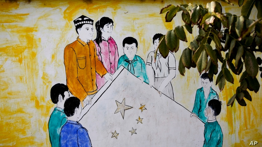 In this Sept. 20, 2018, photo, a mural showing Uighur and Han Chinese men and women carrying the national flag of China…